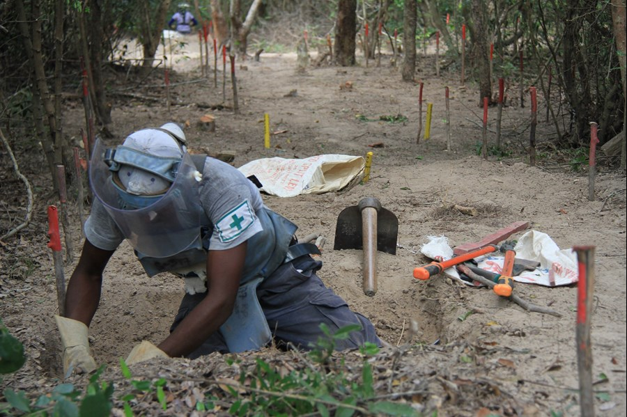 A deminer conducts manual excavation at BND11e.The yellow sticks in the background mark where a number of mines have been found and removed