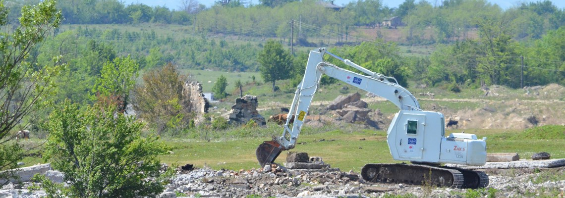 Japanese-funded armoured excavator Hitachi ZX130 conducts mechanical clearance.