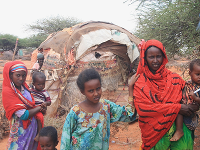Nimco (right) outside her house with her children and some of her neighbours, all of whom live on top of a minefield
