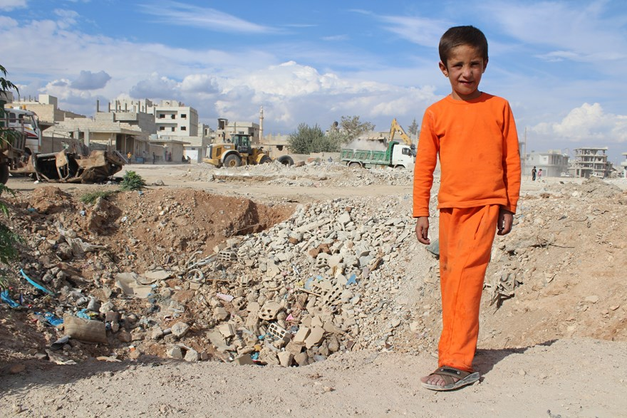 Syrian child playing near a bomb crater
