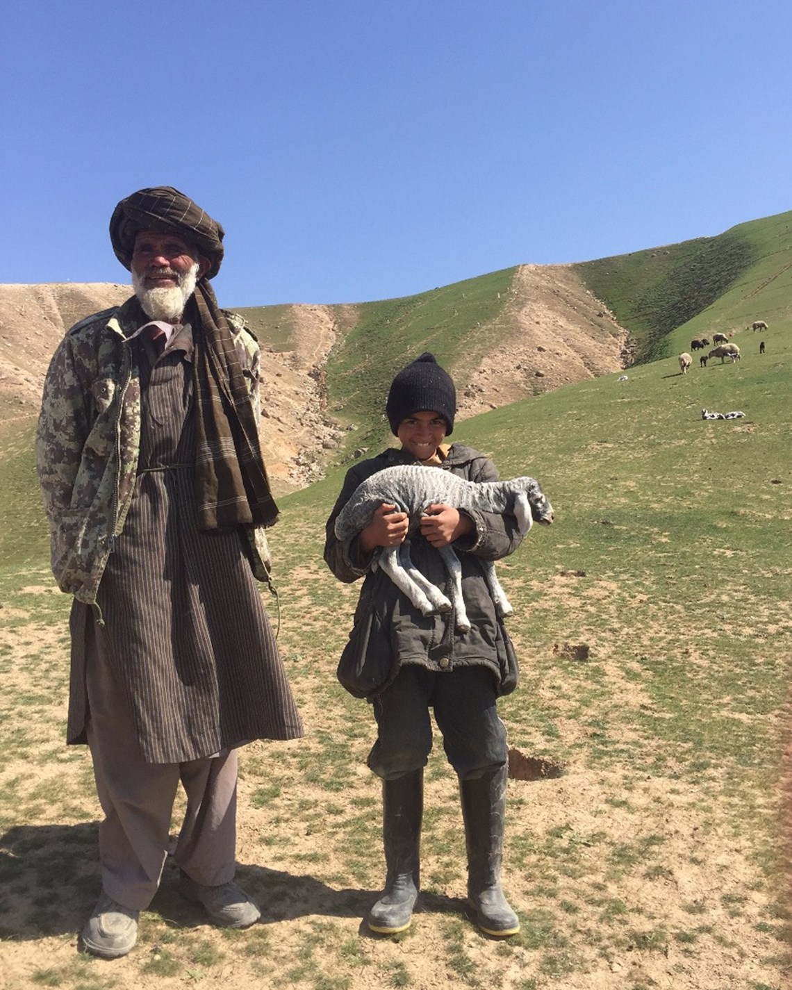 Abdul Hakim stands with his grandson on the land HALO cleared of mines