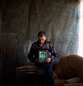Mher holding a picture of his son, Norashen village, Karabakh