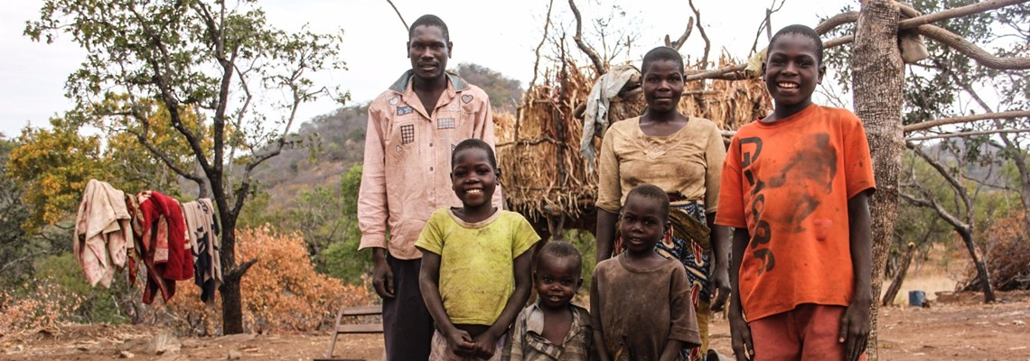 Romeo with his wife and four of his children. The family's new homestead stand is much larger than their previous stand in Chisaro village. Romeo is planning to cultivate the land around the house and hopes to expand into the cleared minefields when the land is officially handed over.