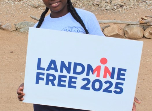 Deminer Teresa Nene from Angola holds sign showing her support for a Landmine Free 2025, image by The HALO Trust.