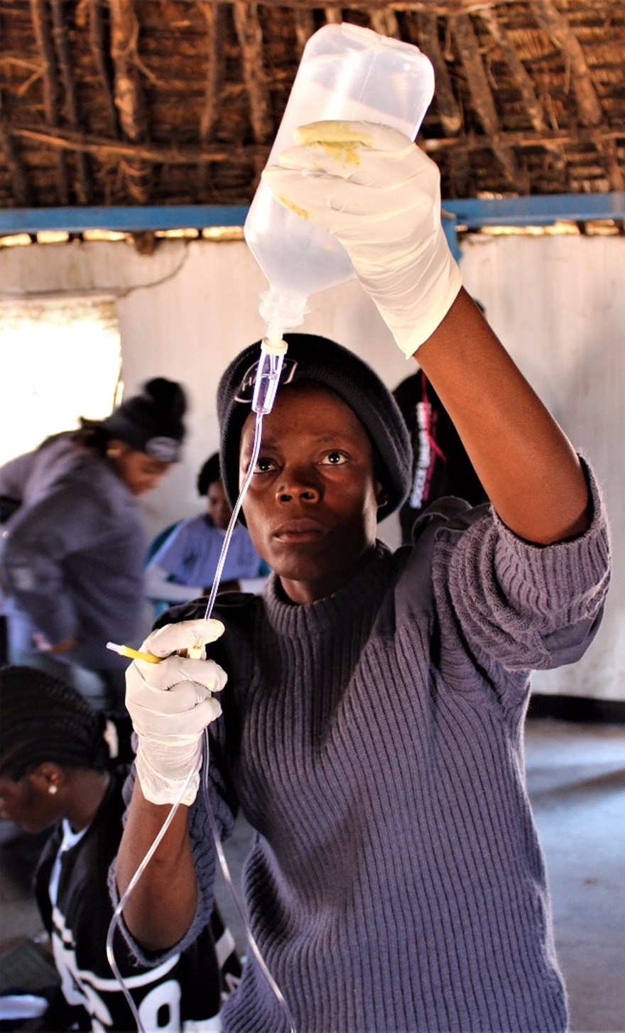 A female Paramedic-Deminer trainee prepares an IV drip during medical training.