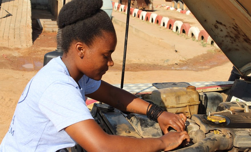 A female driver for the 100 Women In Demining teams checks the engine of her vehicle.