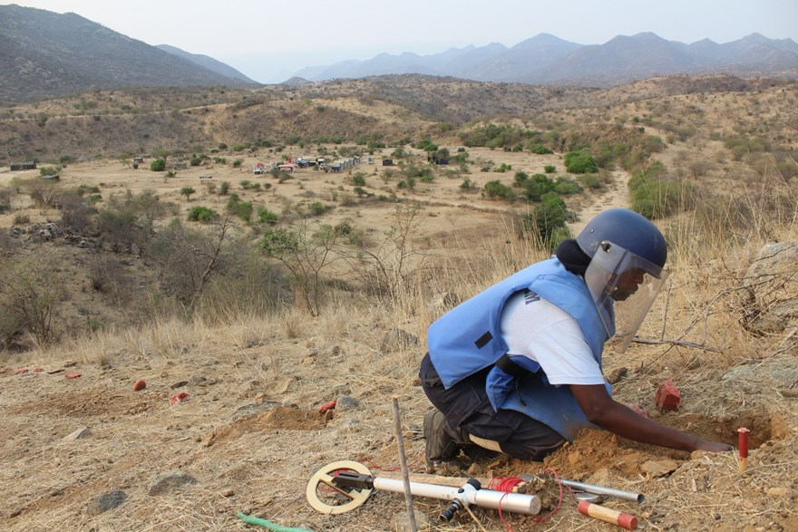 A deminer excavates a metal signal overlooking the Halo camp in Kanenguerere.